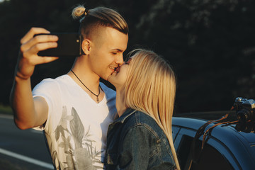 Man taking selfie?and kissing girlfriend