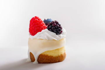 Mini cheesecake with berries and cream on a white background