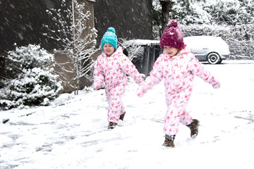 first snow, children have fun on the street, making the first snowman