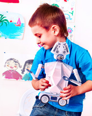 Child play with robot toy. Kid engaged in robotics in programming classes. Boy is programming own tech smart toys transformer with artificial intelligence at school.