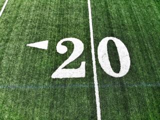 20 yard chalk mark on an green American football field taken from an aerial drone