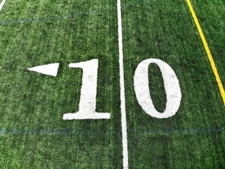 10 yard chalk mark on an green American football field taken from an aerial drone