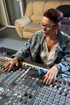 Young woman working in studio of sound recording sitting at huge control board.
