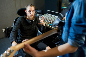 Bearded man sitting at console in recording studio and talking to crop man with guitar preparing new song.