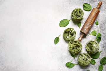 Food background with homemade spinach pasta tagliatelle, wooden rolling pin and spinach leaves.Top view with copy space.