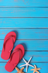 Flipflops starfish summer seashore blue wood background vertical