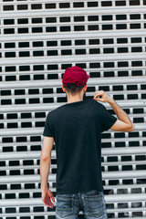 Young muscular bearded man wearing black tshirt and jeans posing in center of modern city. Empty concrete wall on the background. Hotizontal mockup, back view.