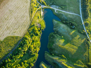Top view, aerial photo from drone or aerostat to summer nature landscape panorama, green meadows and river in countryside at sunset time, beautiful natural background