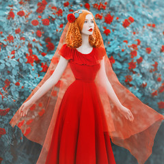 Young beautiful redhead girl with very long hair braided in plait with rose on her head. Fabulous renaissance woman in a red dress against the backdrop of a beautiful rose bush