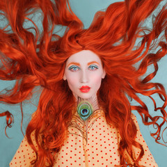 Young beautiful unusual red-haired girl with very long curly hair on a blue background. Fairytale model in a yellow dress with an unusual hairdo with a peacock feather. Pale skin