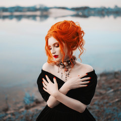 A woman is a vampire with pale skin and red hair in a black gothic dress and a necklace on her neck. Girl witch with vampire claws and red lips. Gothic look. Outfit for halloween.