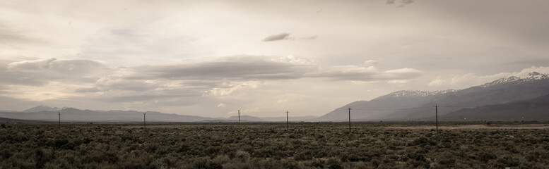 Powerlines stretch across open spaces in central California with mountains in the background under a hazy, cloudy day