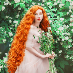 Young beautiful redhead girl with very long curly hair. Fabulous pale skin model in renaissance dress against the background of a blooming spring garden. Hair care concept