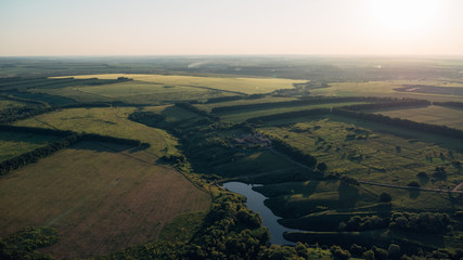 Top view, aerial photo from drone or aerostat to summer nature landscape panorama, green meadows and river in countryside at sunset time