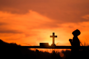 The boy sit and praying to God with cross, christian silhouette concept.