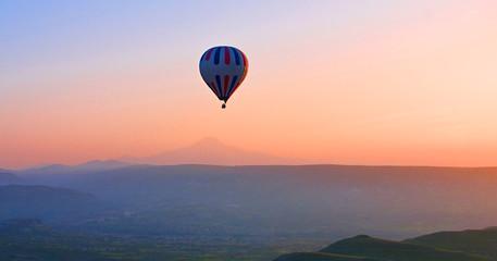 Hot air balloon flying over amazing landscape at sunrise, Cappadocia, Turkey