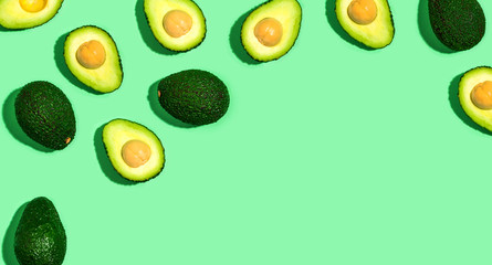 Fresh avocado pattern on a green background flat lay