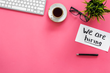 Search for worker, employee concept. We are hiring lettering on work desk on pink background top view copy space