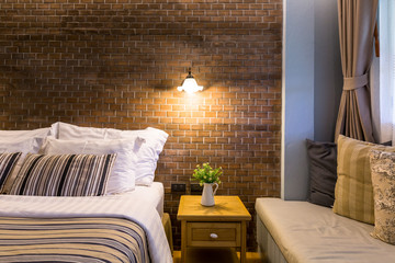 Night time stylish bedroom interior design with brown patterned pillows on bed.