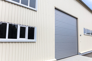 white metal warehouse wall with windows and closed gray gate
