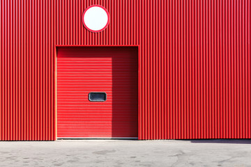 red metal warehouse wall with closed roller shutter door