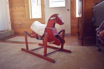 Vintage hand-made red rocking horse toy in a rustic cabin
