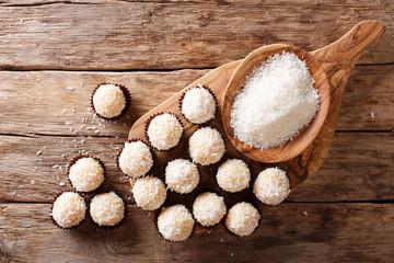Delicious coconut kisses (beijinhos de coco or branquinhos)  - festive Brazilian sweets close-up. horizontal top view