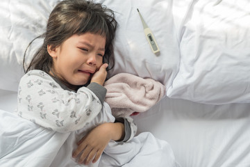 sick girl lying in bed with a thermometer