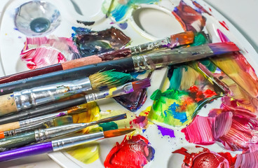 Art brushes and paints for painting on the used palette with paints close-up.