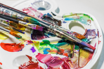 Palette of the artist with oil paints and brushes for drawing. close-up as an artistic background.