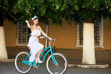 Woman in white long dress and an accessory on her head, riding on asphalt on a blue bicycle summer in the city, on the background of green trees, walls of buildings.