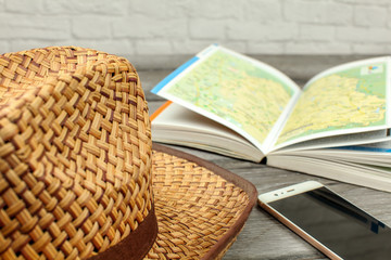 Straw hat, guide book with map, and mobile phone on gray wood desk. Travel planning concept.