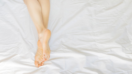Woman legs in white bed sheets. skincare concept