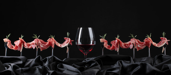 Prosciutto with rosemary and glass of red wine on a black background.