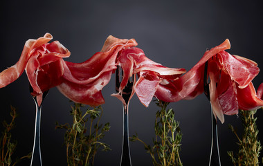 Prosciutto with thyme twigs on a dark background.