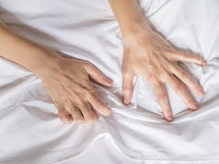 Hand clutches grasps a white crumpled bed sheet in a hotel room, a sign of ecstasy, feeling of pleasure or orgasm. Orgasm is the greatest point of sexual pleasure or a climax of sexual excitement