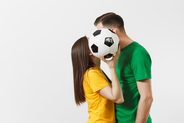 European young couple, woman man in love, football fans in yellow green t-shirt cheer up support team kissing behind soccer ball isolated on white background. Sport, family leisure, lifestyle concept.