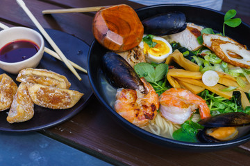 Noodle soup with seafood including mussels, prawns, squids, eggs, vegetables.