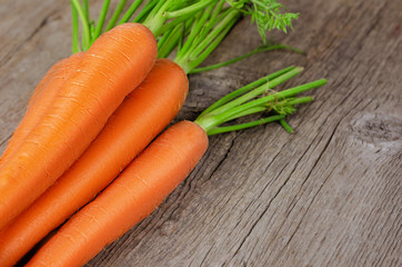Fresh carrot bunch on wooden background.