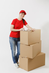 Full length portrait of delivery young woman in red cap, t-shirt isolated on white background. Female courier standing near empty cardboard boxes with tablet pc computer. Receiving package. Copy space