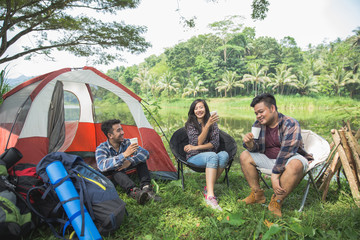 Friends Relaxing Outside Tents On Camping