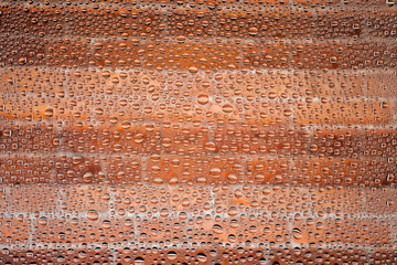Close up of a water drops on a red old stripted brick background, covered with drops of water...