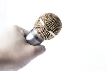 A man's hand holds a microphone on a white background.