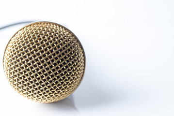 Microphone on a white background with a gold-plated nozzle.