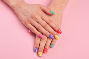 Poster de jardin Manicure Female hands with colorful polish nails. Woman well-groomed hands with multicolor nails on salon table. Manicure nail painting.