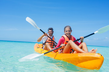 Happy girl and her father kayaking at tropical sea on yellow kayak