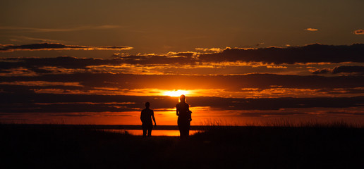 Two people walk on the background of the orange sun, their contours and silhouettes are visible.