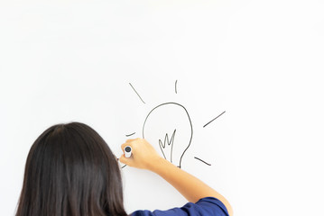 business, people, idea, startup and education concept - close up of hand with marker drawing light bulb at office