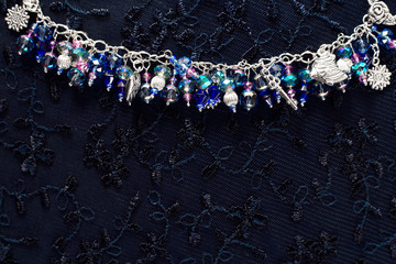 Bracelet with pendants and beads made of glass and metal. Textured background with jewelry.