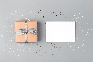 Gift box wrapped in kraft paper and tied with gray ribbon and white blank on gray background decorated with confetti. Top view, holiday concept.